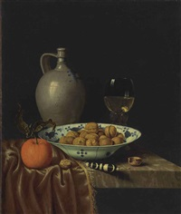 walnuts in a wan-li porcelain bowl, a stoneware jug, an orange, a knife with an ebony and ivory handle and a roemer, on a partially draped ledge by hubert van ravesteyn