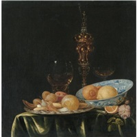 still life with oranges and lemons in a blue and white porcelain dish, a large gold pronckblokaal and a silver platter, all arranged on a draped table by simon luttichuys
