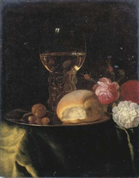 a roemer of white wine, a bread roll and nuts on a silver plate, together with roses on a green-draped table by simon luttichuys