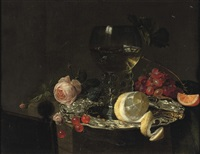 a roemer with white wine, a partially peeled lemon, cherries and other fruit on a silver plate with a rose and grapes on a stone ledge by simon luttichuys