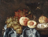 peaches, grapes, a wineglass, an oyster and a piece of bread, all on a partially draped marble ledge by abraham van beyeren