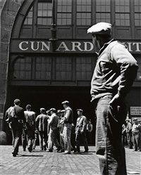 a gang of longshoremen walk to work on a dock, while others stand around hoping they will be as lucky, cunard line pier, new york by andreas feininger