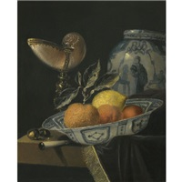 a still life of an orange, a lemon and two peaches in a wan-li porcelain bowl on a table with a fringed carpet and a nautilus cup by juriaen van streeck