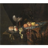 a still life with oranges, peaches and a lemon in a blue-and-white china bowl, a silver-gilt nautilus cup on a silver gilt plate together with a lemon, a bread roll and a knife, together with a roemer by juriaen van streeck
