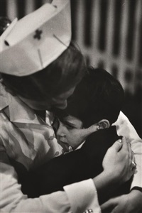 child survivor from road accident being comforted by red cross nurse by w. eugene smith