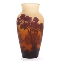 a glass vase overlaid with red glass in the shape of trees in a landscape by émile gallé