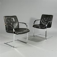 a pair of armchairs with curved steel frame, upholstered with black leather by preben fabricius and jørgen kastholm