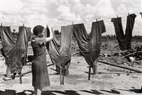 mrs. foster hanging up her husband's overalls, irwinville farms, georgia by john vachon