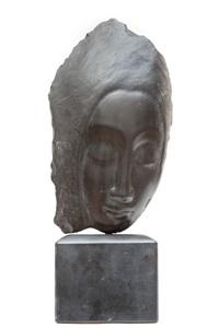 een zwart hartstenen sculptuur van een gestileerd vrouwengelaat op zwart marmeren sokkel by jules vermeire