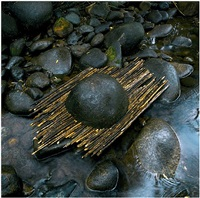 river boulder reworked with sticks raining, woody creek, colorado by andy goldsworthy