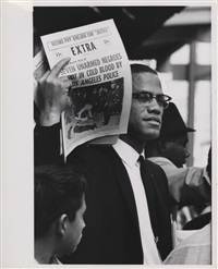 malcolm x holding up black muslim newspaper, chicago, illinois by gordon parks